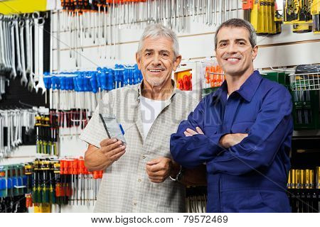 Portrait of confident vendor with customer standing in hardware shop