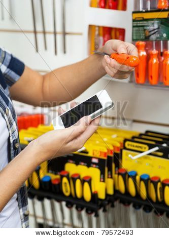 Cropped image of female customer holding cellphone and screwdriver in hardware store