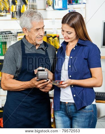 Senior salesman holding electronic reader while customer paying through smartphone in hardware store