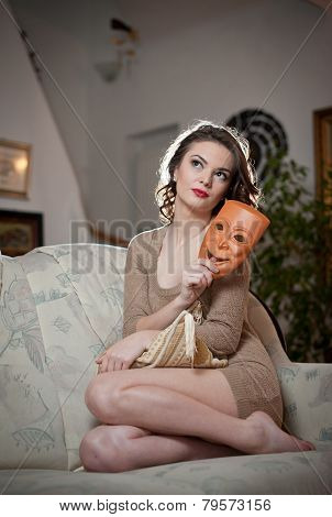 Young sensual woman sitting on sofa holding a mask. Beautiful long hair girl