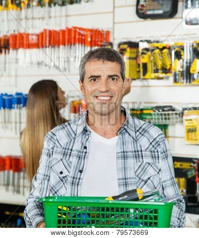 Portrait of happy mature man carrying basket full of tools with woman in background at hardware store
