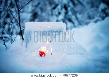 Ice lantern with red candle burning inside