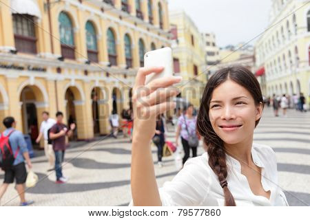 Woman tourist taking selfie pictures in Macau, China in Senado Square or Senate Square. Asian girl tourist using smart phone camera to take photo while traveling in Macau. Travel and tourism concept.