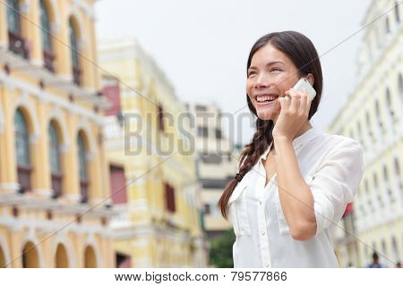 Business woman talking on smart phone in Macau, China. Asian businesswoman using smartphone talking having conversation in Macau on Senado Square or Senate Square.