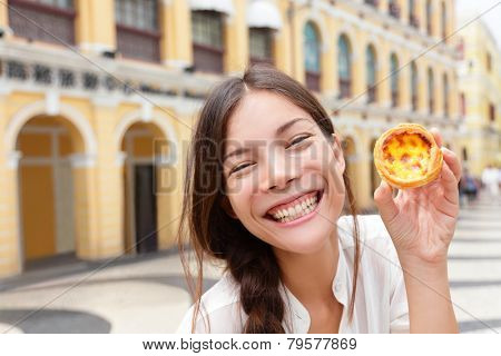 Local Macau food - woman showing Pastel de nata. Traditional Portuguese egg tart pasty cake from bakery in Macau, China in Senado Square or Senate Square. Asian girl tourist traveling in Macau.