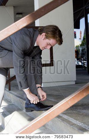 Man Ties His Shoelaces