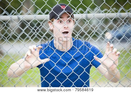 Young Man Hanging On Fence At Sportsfield