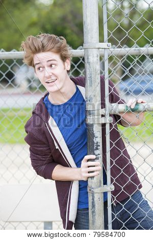 Portrait Of Young Man Standing By A Fence