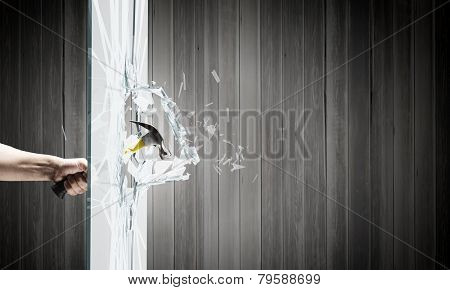 Close up of hammer in human hand breaking glass