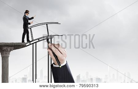 Businessman in blindfold walking on drawn bridge over gap