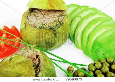 meat meal: round zucchini filled mince meat over white dish served with vegetables