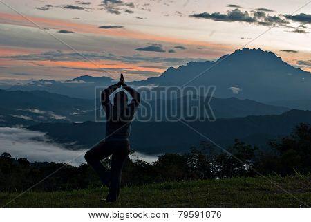 Unidentified Woman Practising Yoga With Mount Kinabalu As Background