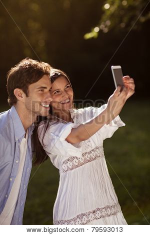 Young Couple Taking A Selfie In The Park