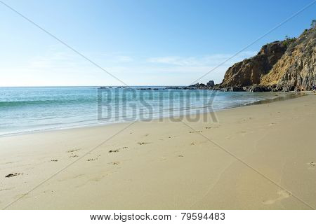A wide scenic panorama of gently flowing ocean surf against a beautiful sandy beach in a secluded cove in Laguna Beach, California during a bright, sunny day.