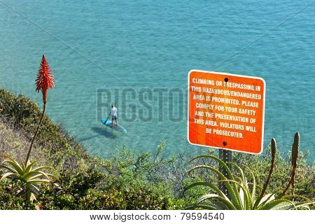 A sign posted on the side of a cliff warning hikers to keep a safe distance from the edge.
