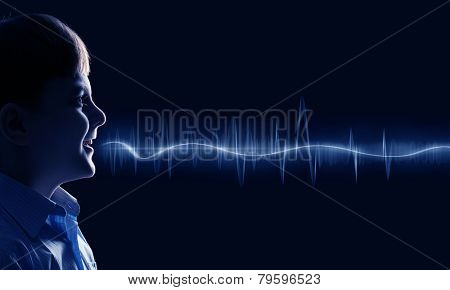 Side view of boy of school age and voice coming out of his mouth