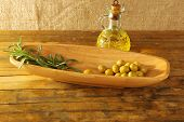 foto of oblong  - Green olives and branch in oblong bowl with oil can on rustic wooden table - JPG