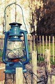 picture of kerosene lamp  - Old blue kerosene lamp hangs on wooden outdoor fence vintage toned photo with filter effect - JPG