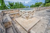 stock photo of mausoleum  - Public stone well in addition to the family mausoleum Petranovic at the old cemetery in Supetar - JPG