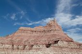 pic of wispy  - Layers of clay and rock carved out by erosion creating a dramatic peak against a blue sky with white wispy clouds - JPG