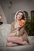 pic of tight dress  - Young sensual woman sitting on sofa holding a mask - JPG