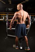 picture of weight lifter  - Toned and ripped lean muscle fitness man standing by a weight bench at the gym - JPG