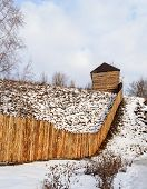 picture of log fence  - Rough wooden fence and a barn on the snow - JPG