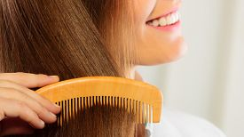 picture of hair comb  - Closeup young business woman refreshing her hairstyle combing her long brown hair with wooden comb