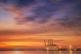 pic of shipyard  - Container Cargo freight ship with working crane bridge in shipyard at dusk for Logistic Import Export background - JPG
