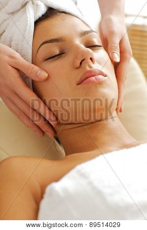 Young woman receiving face massage, eyes closed