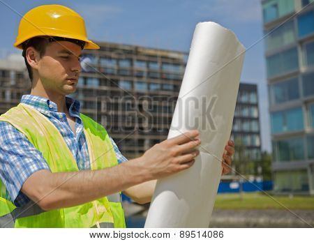 Engineer looking at blueprint on construction site