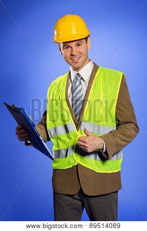 Portrait of businessman in coveralls holding clipboard and showing thumbs up sign