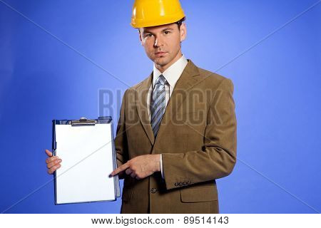 Portrait of businessman in hardhat pointing at clipboard