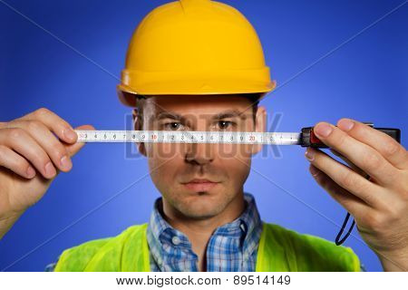 Architect in hardhat holding tape measure