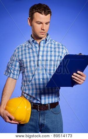 Architect holding hardhat and looking at clipboard