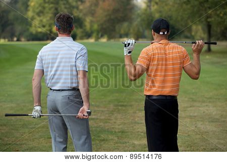 Young men standing in golf course with sticks, rear view