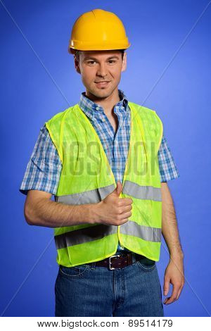 Portrait of architect in coveralls and hardhat showing thumbs up sign