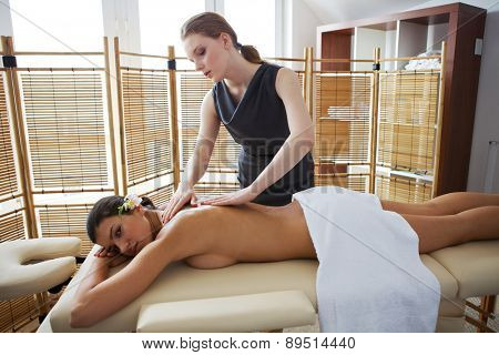 Portrait of young woman receiving massage from masseuse