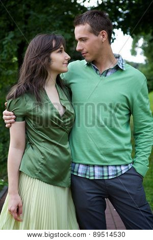 Young couple with arm around and looking at each other