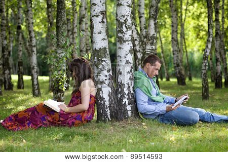 Young couple reading books in park by tree trunk