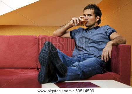 Portrait of young man drinking wine in hotel room