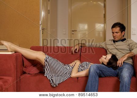 Woman sleeping on husband's lap in hotel room