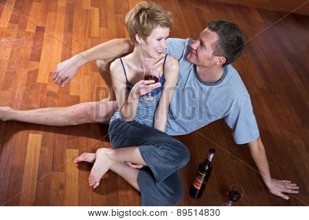 Young couple drinking wine on floor