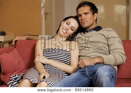 Young couple watching TV in hotel room