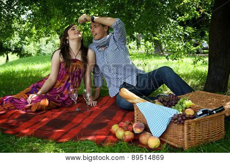 Young couple sitting on picnic blanket while boyfriend feeding