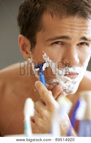 Close-up of a young man shaving his face