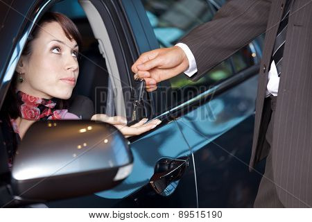 Young woman receiving the car keys from car salesman