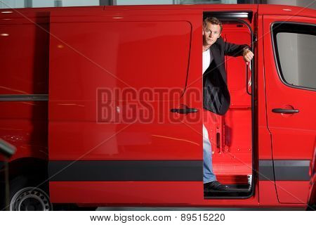 Young man looking through van door, portrait