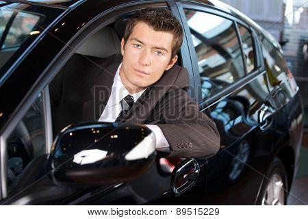 Portrait of man sitting in new car