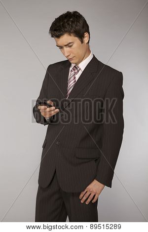 Young caucasian businessman playing with phone